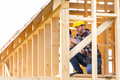 Builder working on wooden construction of frame house - PhotoDune Item for Sale