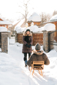 girl carries a guy on a sled on a snowy street - PhotoDune Item for Sale
