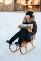 girl sitting in a sled, smiling and holding a  log in her hands - PhotoDune Item for Sale
