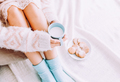 Young woman on the bed with with cup of milk in hands enjoys her stay at home. - PhotoDune Item for Sale