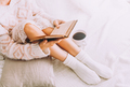 Young woman on the bed with old book and cup of coffee enjoys her stay. - PhotoDune Item for Sale