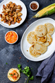 COLOMBIAN FOOD. Maize AREPAS and fried pork chicharron ans colombian tomato sauce. Top view. Black - PhotoDune Item for Sale