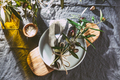 Table setting with gray Linen tablecloth and napkin, white plate, cutlery and olive tree branch - PhotoDune Item for Sale