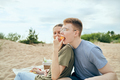 Lovestory of young couple feeding each other on beach - PhotoDune Item for Sale
