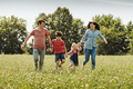 Young family running hand in hand through a field - PhotoDune Item for Sale