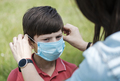 Mother fitting a young boy with a face mask - PhotoDune Item for Sale
