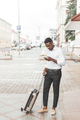 Young black man with luggage using smartphone and listening music - PhotoDune Item for Sale