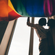 Lesbian couple in silhouette in love standing near the window with the rainbow flag.