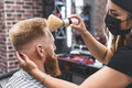 The hairdresser cleans the face of a young guy with a brush after a haircut - PhotoDune Item for Sale