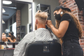 Female barber in mask cuts a man hairs with hair clipper. Hairstyle during social distancing - PhotoDune Item for Sale