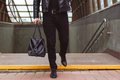 Fashionably dressed man walks from underground crossing with leather bag. Urban casual style - PhotoDune Item for Sale