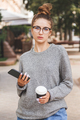 Young girl dressed in casual clothes with smartphone and a cup of takeaway coffee - PhotoDune Item for Sale