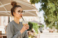 Alone young woman in eyeglasses drinking milkshake and looking away in cozy cafe outdoor - PhotoDune Item for Sale