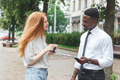 Black african american man on the street making a survey to red haired woman - PhotoDune Item for Sale