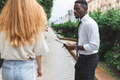 Obsessive black man in business attire interview on the street bothering passersby with questions - PhotoDune Item for Sale