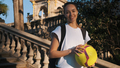 Beautiful girl with backpack and football happily looking in camera in park with architecture - PhotoDune Item for Sale