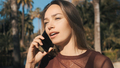 Attractive girl arguing with friend during talk on phone in park - PhotoDune Item for Sale