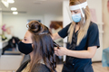Hairdresser, protected by a mask, combing her client's hair with a hair iron in a salon - PhotoDune Item for Sale