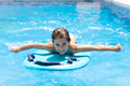 Cute girl playing with a bodyboard in a swimming pool - PhotoDune Item for Sale