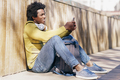 Black man using smartphone resting on the ground - PhotoDune Item for Sale