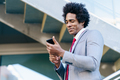 Black Businessman using a smartphone near an office building - PhotoDune Item for Sale