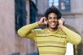 Black man listening to music with wireless headphones sightseeing in Granada - PhotoDune Item for Sale