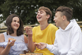 Teenage boys and a girl sharing snacks outdoors - PhotoDune Item for Sale