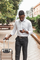 Afro businessman with luggage use phone to hire a taxi. Black man in business trip - PhotoDune Item for Sale