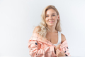 Blonde woman with curly hairstyle dressed in a formal pink jacket on white background. - PhotoDune Item for Sale