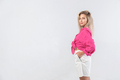 Beautiful blond woman in white shorts and pink blouse posing in studio on white background - PhotoDune Item for Sale