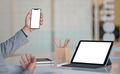 Smartphone in hand and modern tablet blank screen place on the desk. - PhotoDune Item for Sale