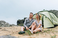 Happy young couple travelers in casual outfits near tent in mountains - PhotoDune Item for Sale