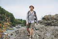 Young man traveler in straw hat with backpack at mountain river - PhotoDune Item for Sale