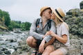 Happy young couple travelers in casual outfits kissing on mountain river background - PhotoDune Item for Sale