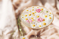 Wildflowers in water in stylish wine glass on background of soft beige fabric - PhotoDune Item for Sale