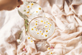 Hand pouring water with daisy flowers in modern wineglass on background of soft beige fabric - PhotoDune Item for Sale