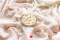 Daisy flowers in water in glass cup on background of soft beige fabric - PhotoDune Item for Sale