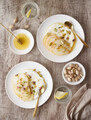 Ricotta with pears, pistachios and honey or maple syrup on two white plate - PhotoDune Item for Sale
