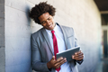 Black Businessman using a digital tablet in urban background - PhotoDune Item for Sale