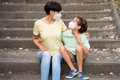 Placeit - Middle-aged mother and daughter sit on the street wearing masks - PhotoDune Item for Sale
