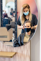 Hairdresser drying her client's hair with a hairdryer wearing protective masks in a beauty - PhotoDune Item for Sale