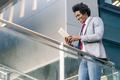 Black Businessman using a digital tablet sitting near an office building - PhotoDune Item for Sale