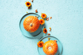 Pumpkins in the Plates on Blue Textured Table Decorated with Flowers - PhotoDune Item for Sale