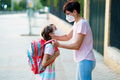 Mother preparing her little girl for the return to school wearing a mask - PhotoDune Item for Sale