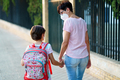 Nine years old girl with bag walking with her mother hand in hand - PhotoDune Item for Sale