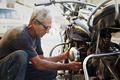 Senior Man Fixing Vintage Motorcycle Engine - PhotoDune Item for Sale