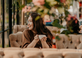 Charming brunette woman with long curly hair sitting in cafe - PhotoDune Item for Sale