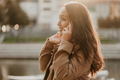 Charming smiling brunette woman with long curly hair dressed casual coat with mobile phone in hands - PhotoDune Item for Sale