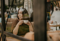 Charming brunette woman with long curly hair sitting at window in cafe with cup of coffee in hands - PhotoDune Item for Sale
