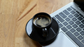 Close - up shot of Hot coffee placed on a laptop keyboard on a wooden table. - PhotoDune Item for Sale
